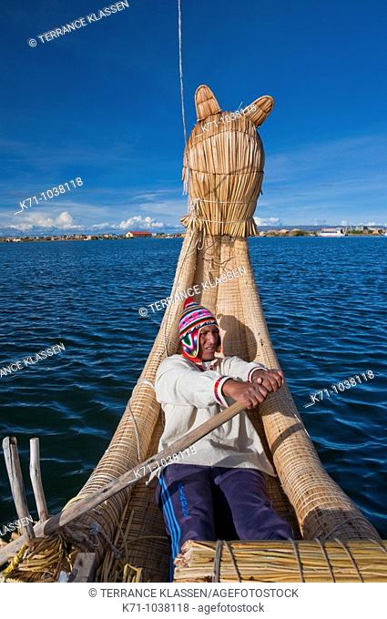 Rowing a large reed boat at the floating Islands in Lake Titicaca, Peru, South America