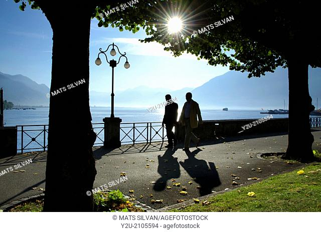 Two persons walking on the lakefront in backlight with trees and mountain in Ticino Switzerland