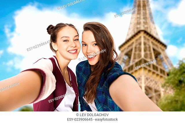 people, travel, tourism and friendship concept - happy smiling pretty teenage girls taking selfie over eiffel tower in paris background