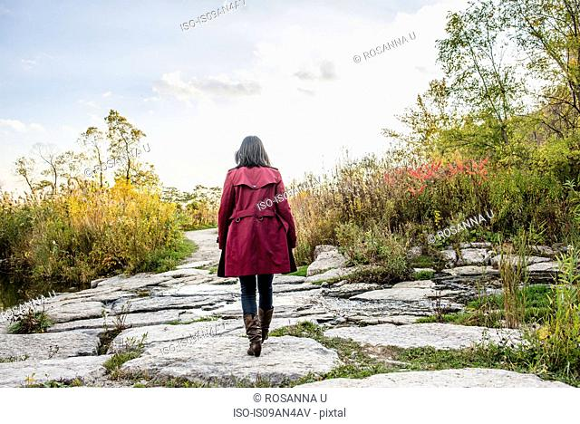 Mid adult woman walking on rocks, rear view