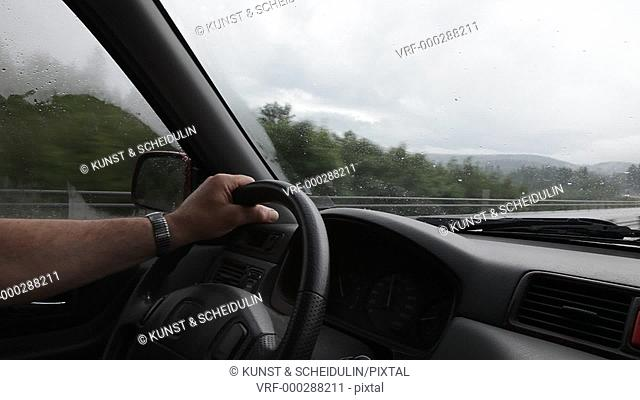 A man is driving on the fenced motorway E4 at the Swedish High Coast on a rainy day. UNESCO World Heritage site Höga Kusten, Västernorrlands Län, Sweden