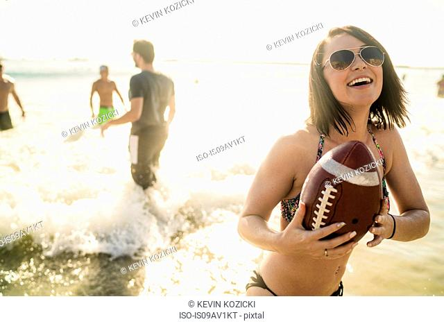 Young woman playing American football with friends at Newport Beach, California, USA