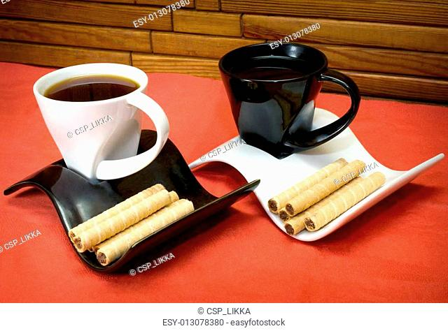 two cups of coffee and wafer sticks with chocolate