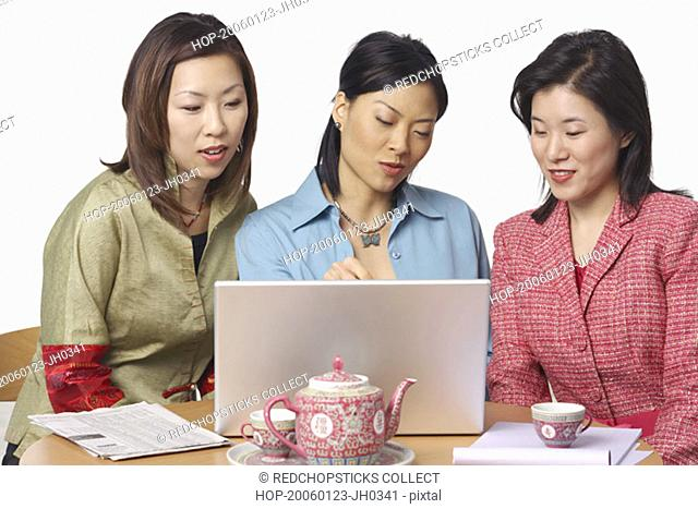 Close-up of three businesswomen in front of a laptop