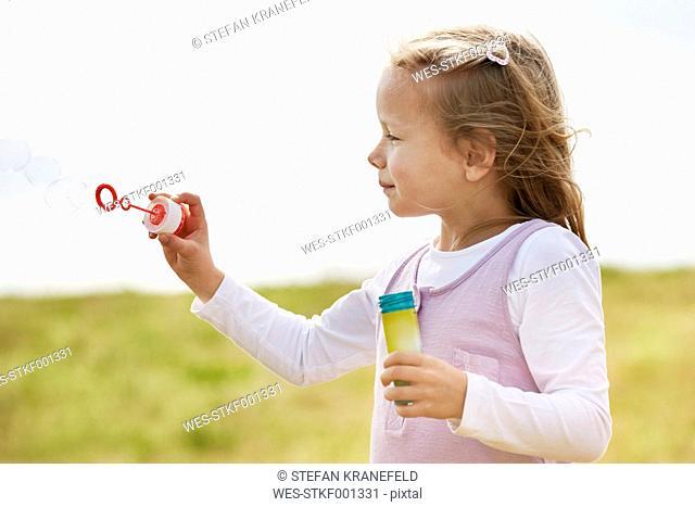 Little children girl blowing soap bubbles