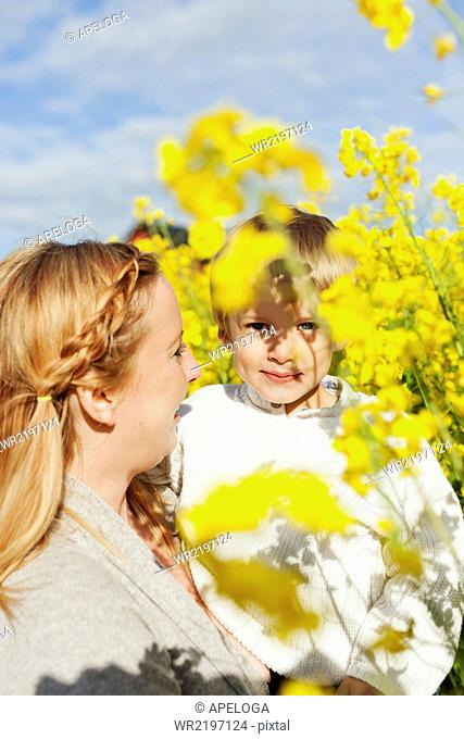 Woman carrying son at rapeseed field on sunny day