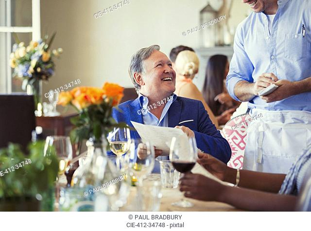 Smiling man with menu ordering from waiter at restaurant table