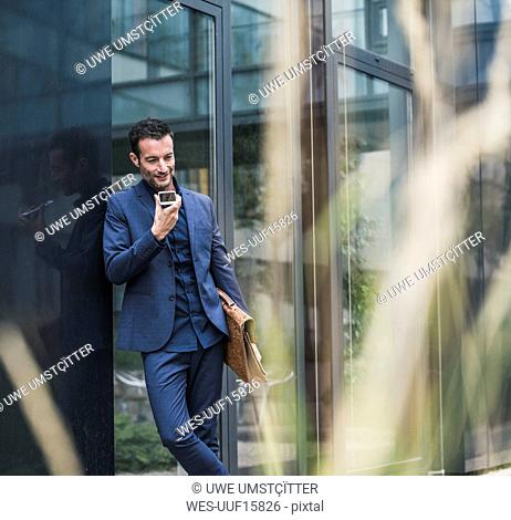 Businessman leaning on building wall, leaving voice notes on his phone