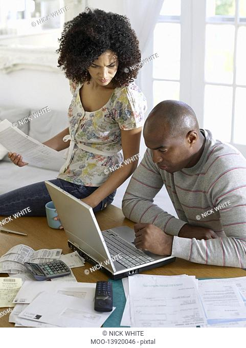 Couple sitting at table using laptop and holding bills elevated view