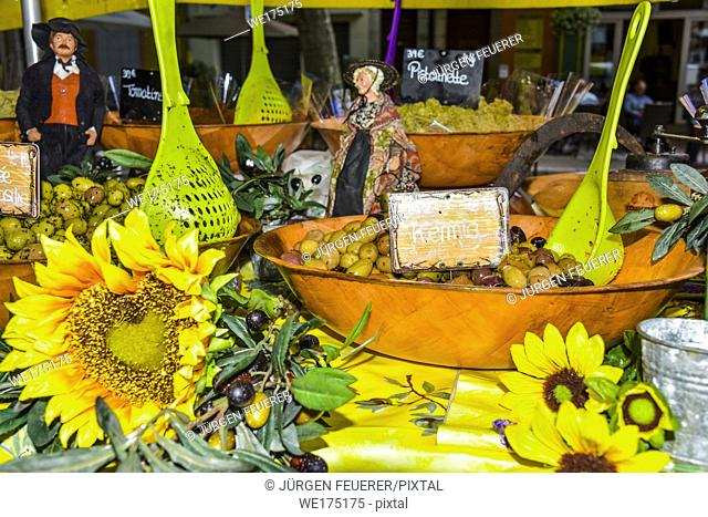 presentation of regional products, olives of the Provence with sunflowers decoration and olive branches, Riez, France, street market at the annual festival of...