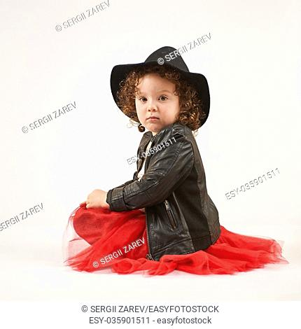 Little girl with black hat sitting and looks