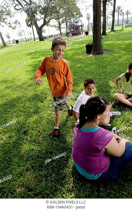 Children sitting in a circle on the grass with their teacher while a boy walks around them