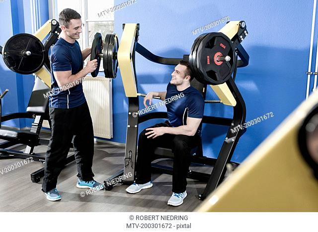 Two young men in gym doing weight training