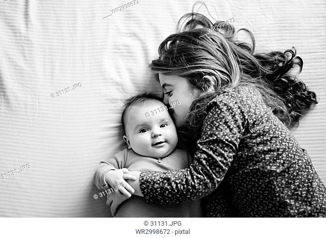 High angle view of girl and baby girl lying on a bed, hugging and kissing