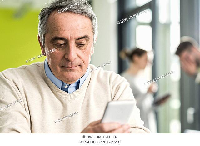 Senior manager reading a message, smartphone