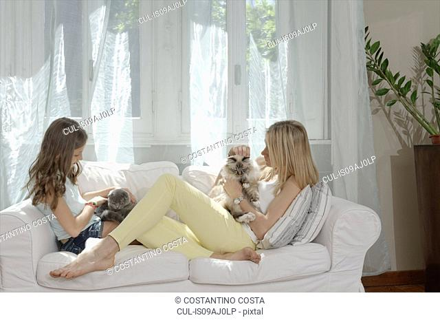 Mother and daughter on sofa petting cats