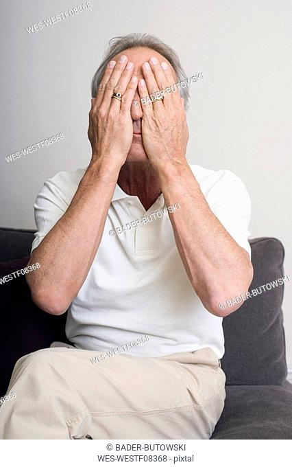 Senior man covering face with hands, portrait