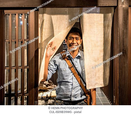 Man stands at door of traditional Japanese house
