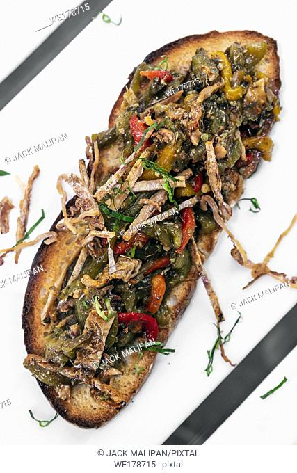 spicy dried squid and roast vegetables toasted open sandwich tapas snack in portugal