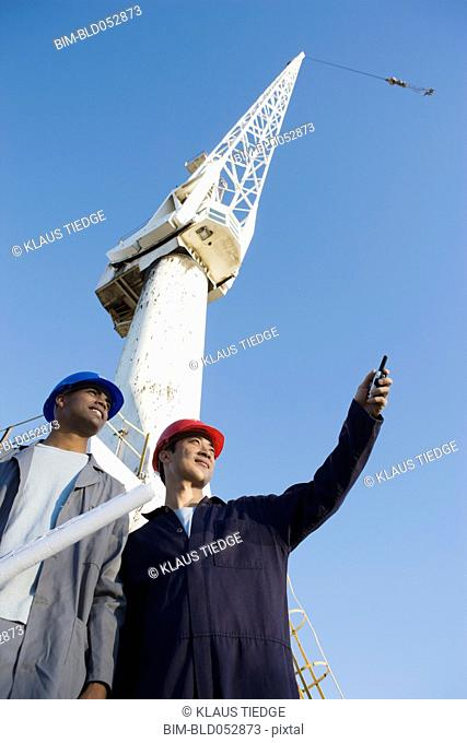 Multi-ethnic male construction workers under crane
