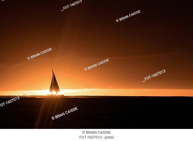 Silhouette of yacht in sea against sky during sunset