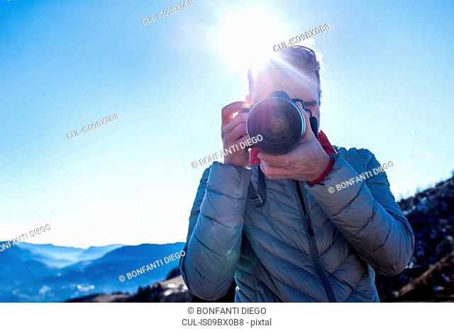 Man taking photograph with camera, Piani Resinelli, Lombardy, Italy