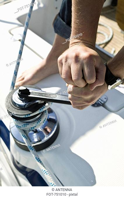 Detail of a man adjutsing the rigging on a yacht