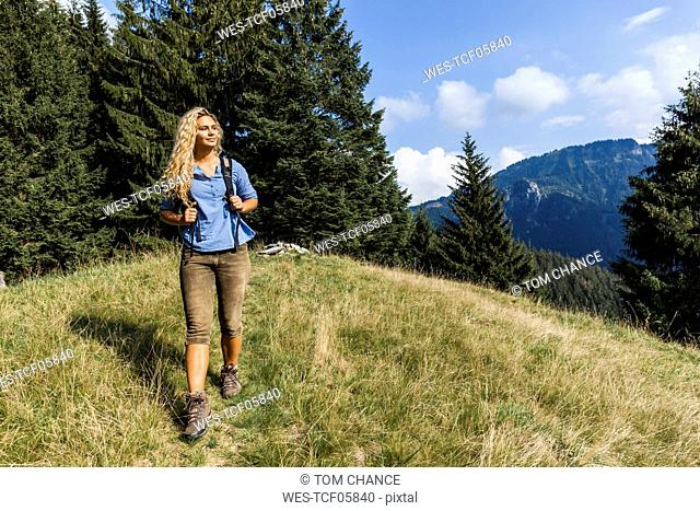Germany, Bavaria, Oberammergau, young woman hiking on mountain meadow