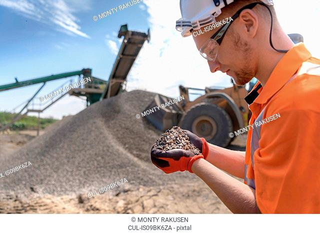 Worker checking handful of screened concrete in concrete recycling site