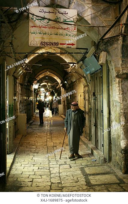 A Musliim man walks through a market in the old city section of Jerusalem