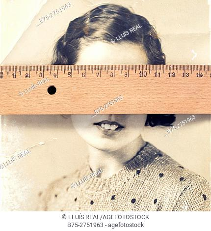 Old black and white portrait of woman with wooden ruler on her eyes