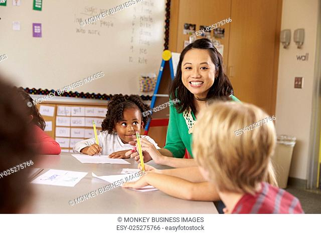 Teacher sitting with kids in elementary school lesson