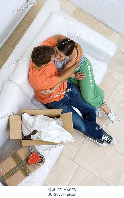Couple hugging on sofa next to moving boxes