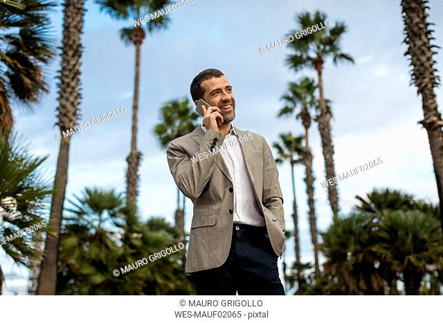 Happy businessman talking on cell phone with palm trees in background