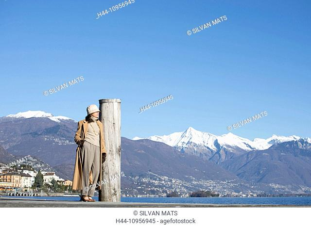 Elegant woman standing up close to a alpine lake with snow-capped mountain in ticino Switzerland, Europe