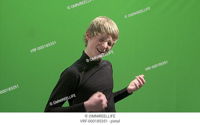 Young blonde male wearing black top playing air guitar green screen