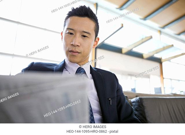 Businessman with newspaper waiting in airport