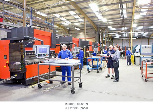 Workers and machinery in factory that manufactures aluminium light fittings