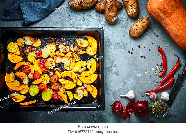 set of sliced vegetables in baking tray and set of whole raw vegetables on a black concrete or stone background. Top view .Space for text
