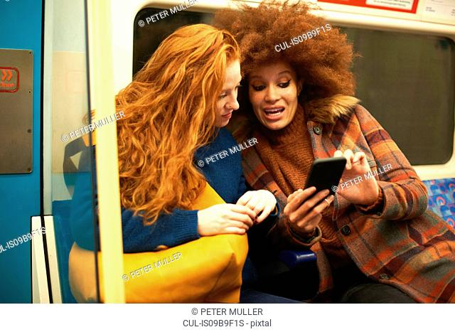 Two young women sitting on train, looking at smartphone