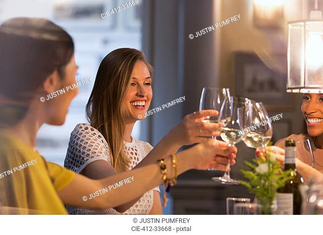 Smiling women friends toasting white wine glasses dining in restaurant