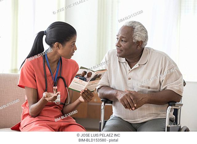Caregiver and older man in wheelchair reading pamphlet