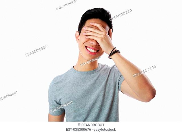 Portrait of a young man covering his eyes with his hand over white background