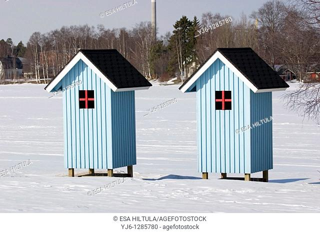 beach huts by the frozen river Finland Europe