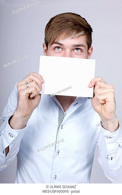 Young man with empty card, close up