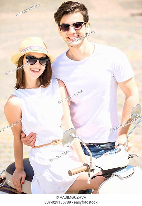Young stylish smiling couple looking at camera while woman sitting on scooter