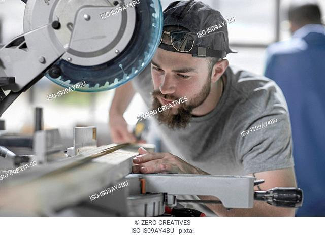 Young carpenter sawing with circular saw in workshop