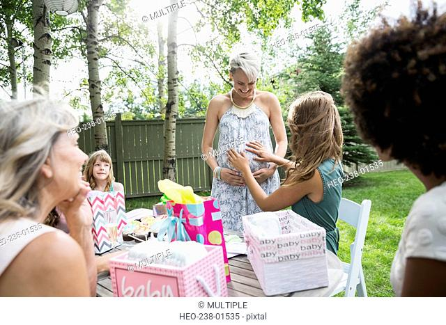 Woman touching stomach of pregnant friend baby shower