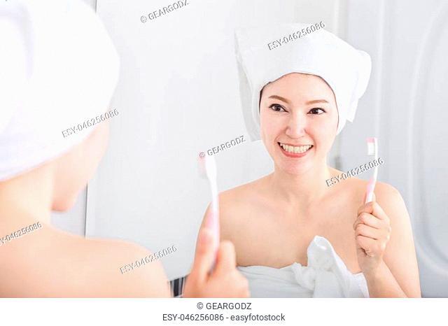 woman in bath towel brushing teeth with mirror in the bathroom
