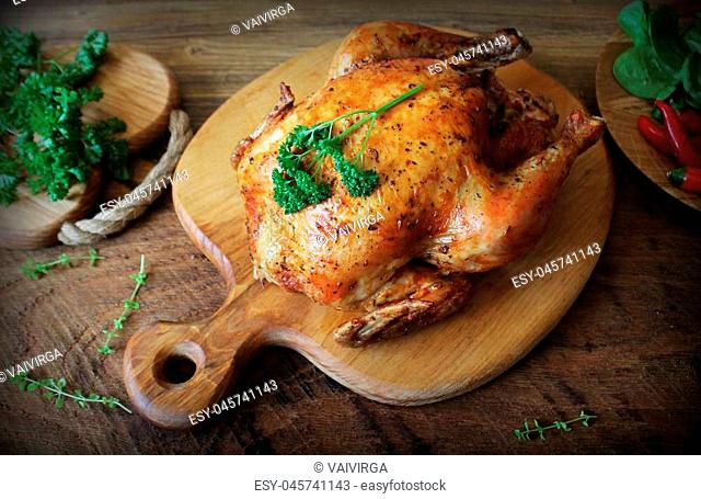 Whole roasted chicken with herb on cutting board . Top view